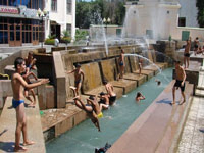 Hot summer. Children are swimming in the fountains in the center of Dushanbe